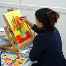 Woman painting flowers in an art class
