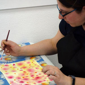 Woman painting with watercolours on a course.