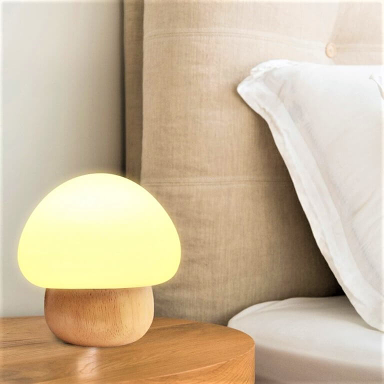 Portable silicon mushroom lamp lying on table beside pillow and bed