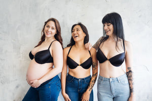 Three women with different body types including one pregnant woman posing happily in black bras and jeans