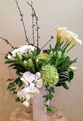 Tall style arrangement of white and green blooms such as Orchids and Calla Lilies