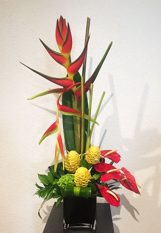 tall one sided arrangement of seasonal tropical flowers