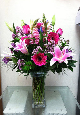 Different shade of pink flowers delivered in a glass vase