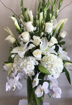 Arrangement of white blooms such as Orchids and Roses with a vase