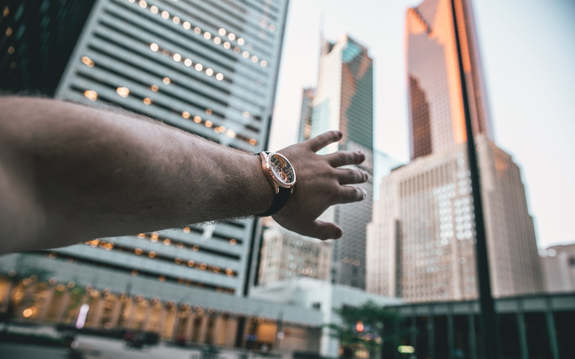 hand with rose gold watch pointing to city skyline view in Toronto Canada