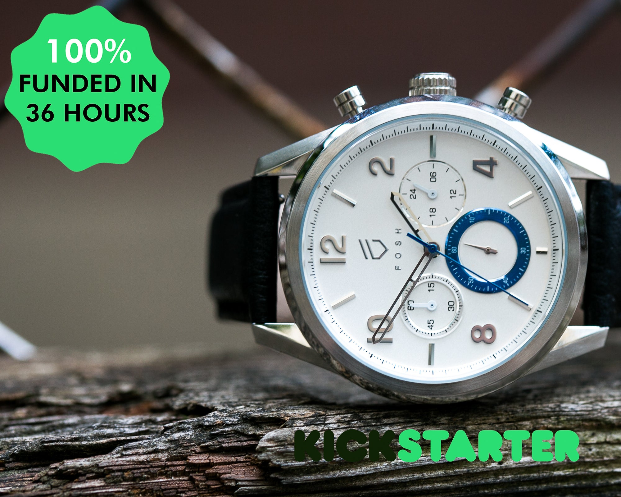 Stainless steel watch with white face and blue second hand on distressed wood with 100% funded on kickstarter sticker