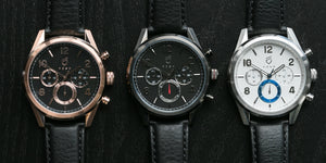 three chronograph watches with black leather straps on black background