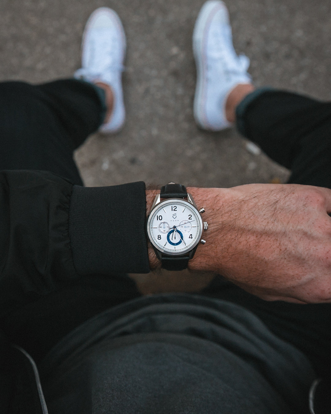 man in black bomber jacket and white converse with silver and blue chronograph watch