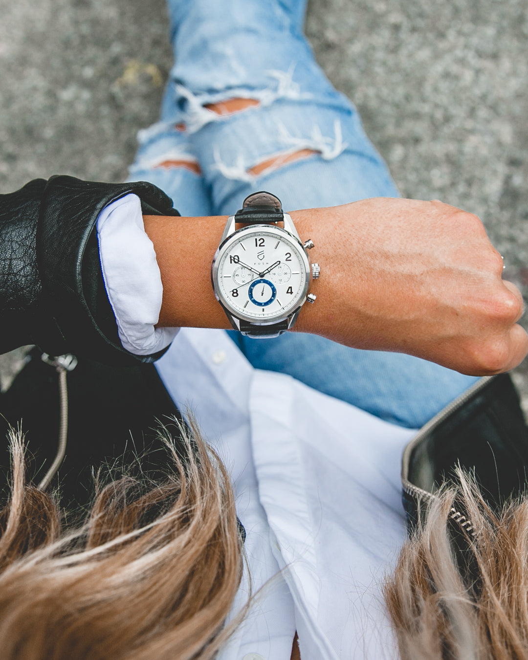 women with ripped jeans and black leather jacket wearing silver and white watch