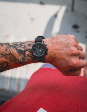 Tattooed men's arm with black watch and red shirt