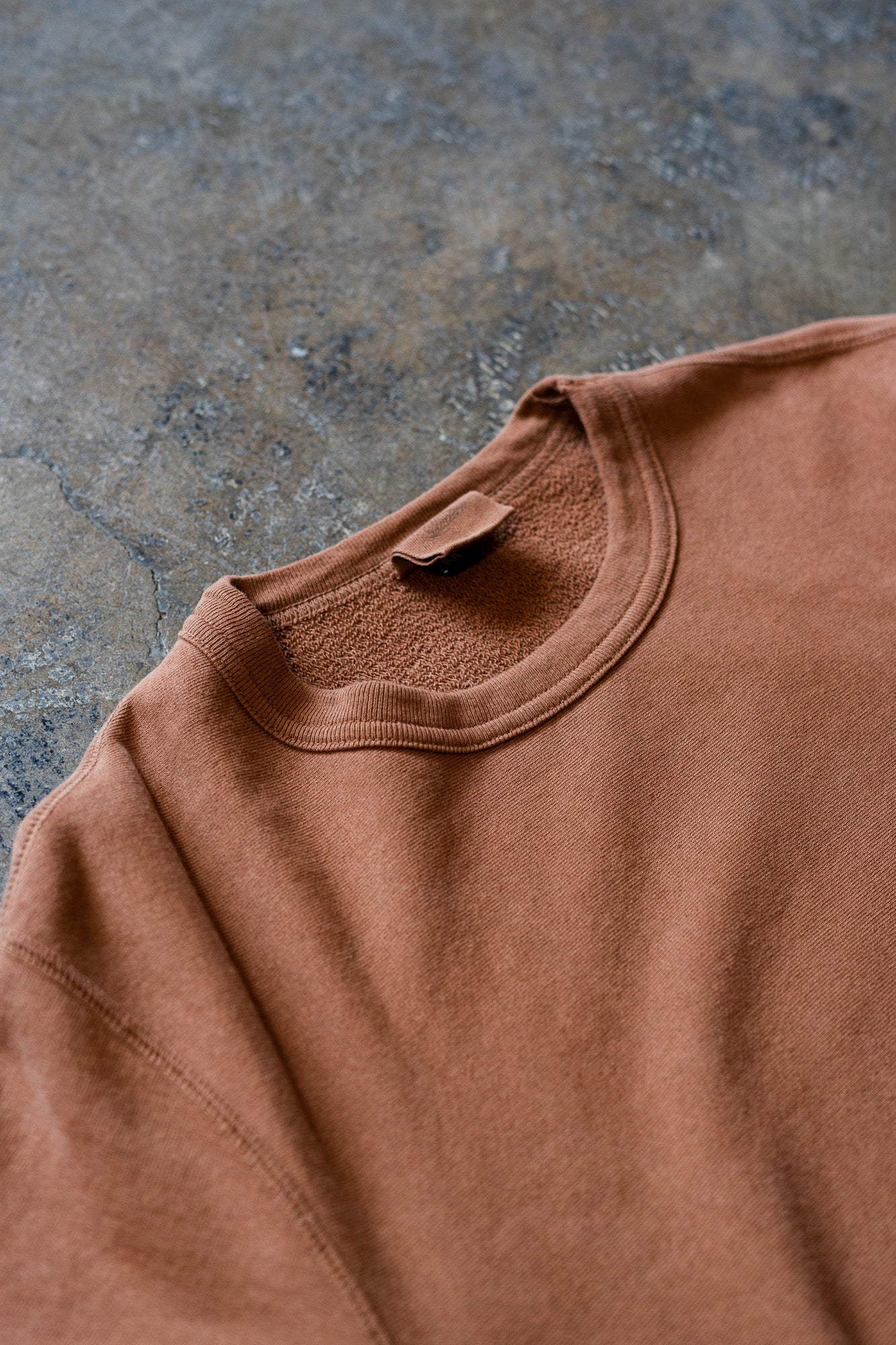 A close up view of the clove crewneck sweatshirt lying on the ground.