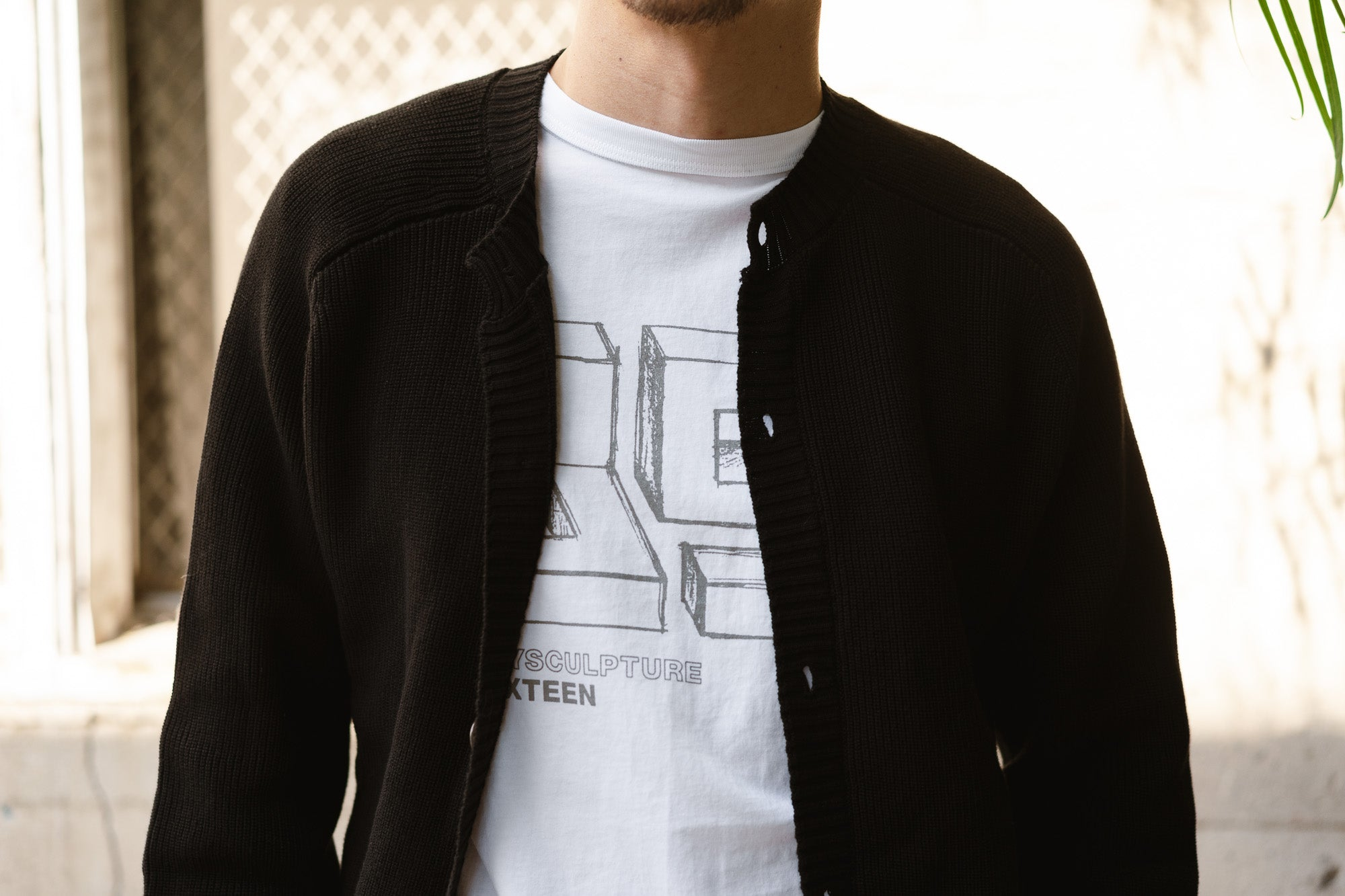A man wears the Playscapes tee under a black cardigan.