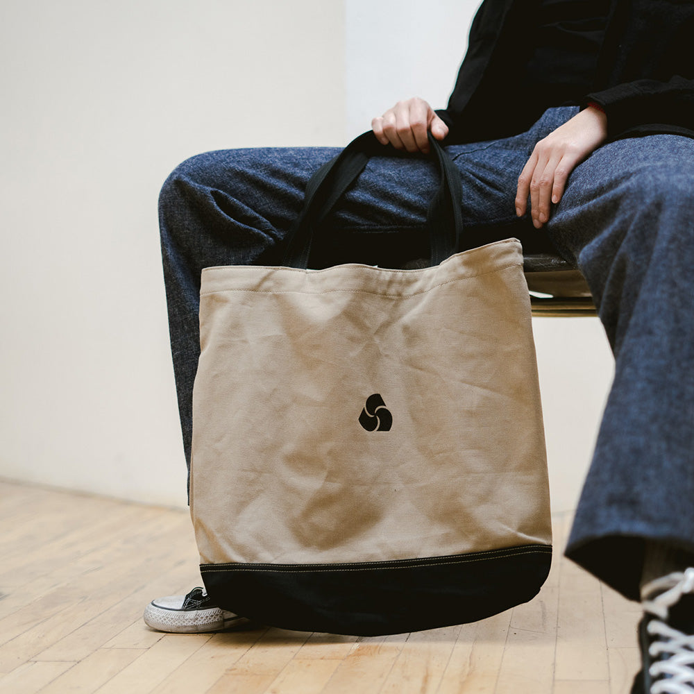 A man holds a tan tote bag.