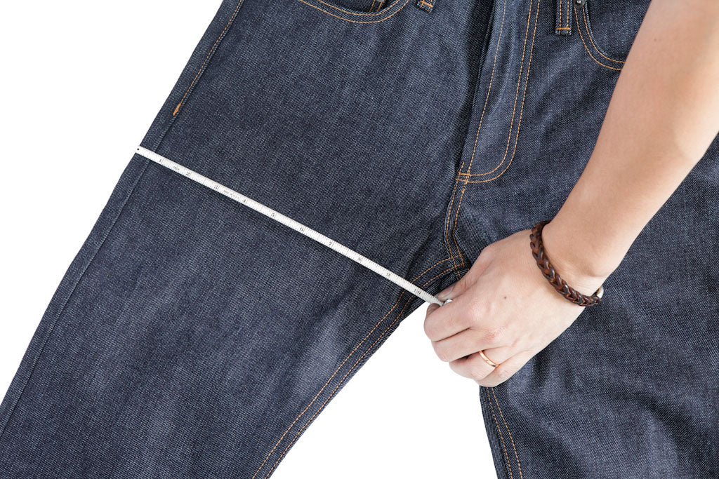 A tape measure runs across the thigh of a jean