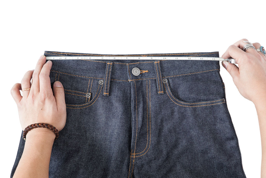 A tape measure runs across a jean waist from end to end