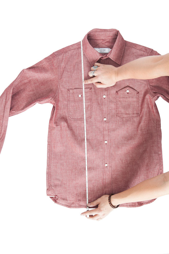 A tape measure running vertically on a shirt from high point shoulder to bottom front hem