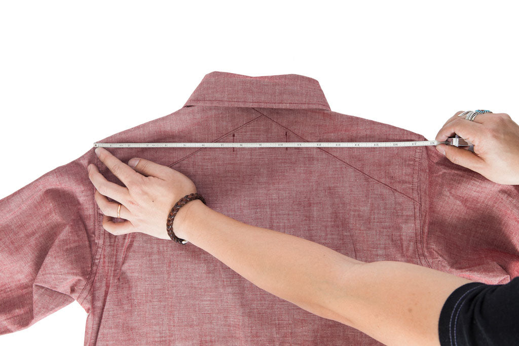 A tape measure running across the back of a shirt from shoulder seam to shoulder seam at the top