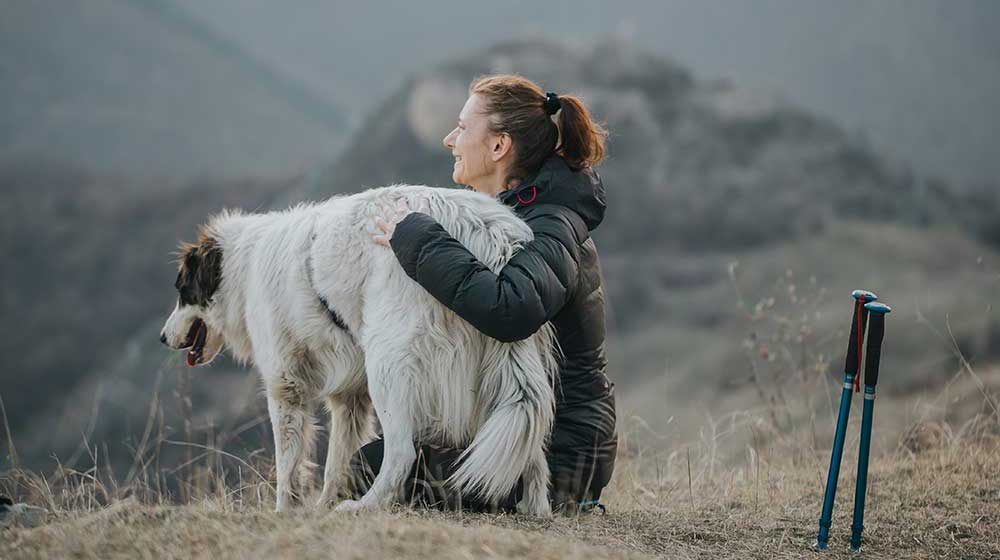 Woman looking at mountainside with her dog