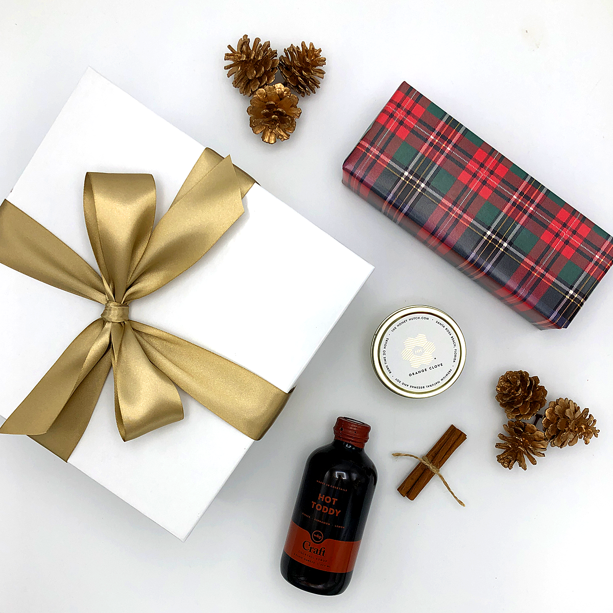 Hot Toddy Gift Box with orange clove candle, Maple Bourbon Pecans wrapped in tartan gift wrap, Hot Toddy Mixer and bundle of cinnamon sticks. Wrapped beautifully!