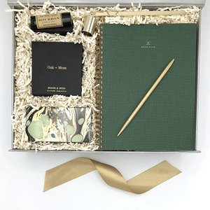 Recovery gift box for him with Appointed dot grid notebook and gold pen, oak and moss candle, matches and a gold snuffer and bourbon lip balm.