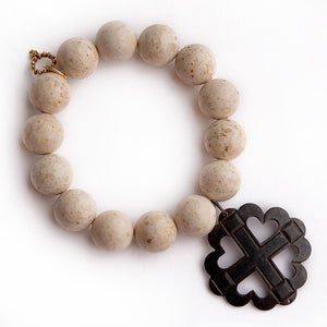 Cream coral paired with a dark bronze heart & cross medal