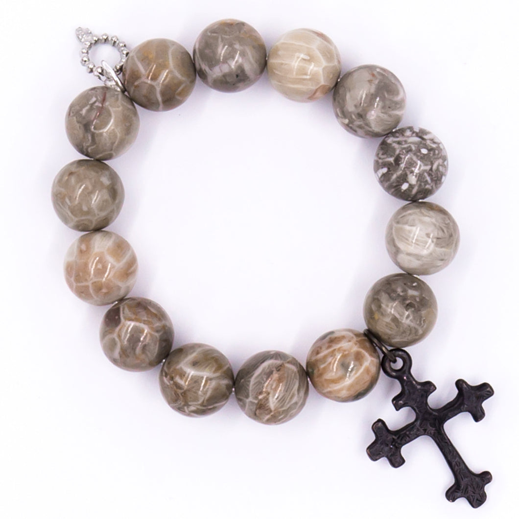 Faceted fossil coral with dark bronze cross