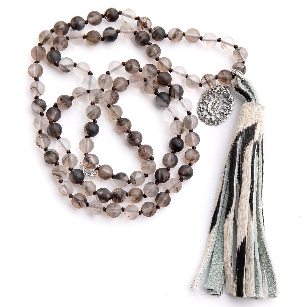 Hand tied matte grey owl agate gemstone necklace hand tied paired with a zebra print leather tassel featuring ornate blessed mother