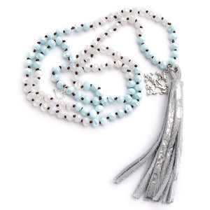 Hand tied faceted two tone aqua and white quartz gemstone necklace paired with a silver speckled leather print tassel featuring  a silver fleur cross