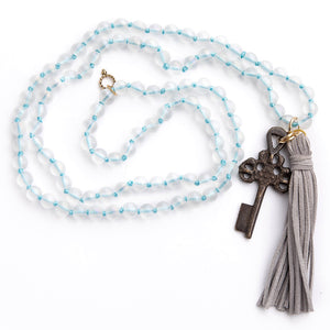 Hand tied frosted quartz gemstone necklace paired with grey leather tassel featuring a dark bronze rustic cross