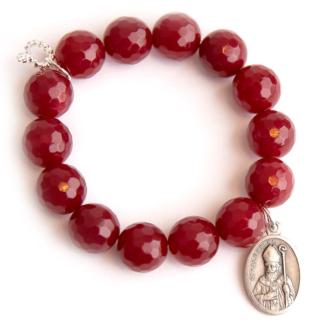Faceted ruby red jade paired with an oval Saint Valentine medal