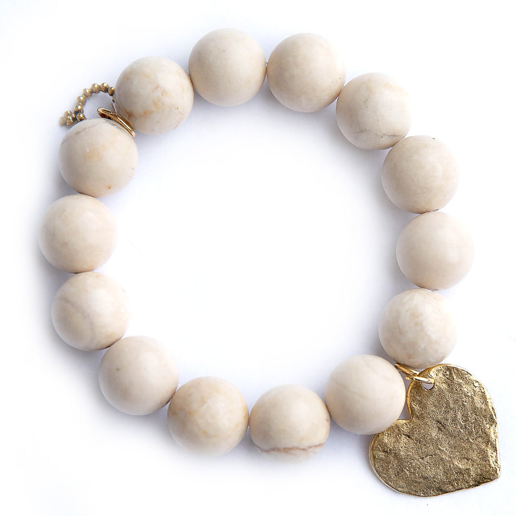 Cream coral paired with a brass hammered heart