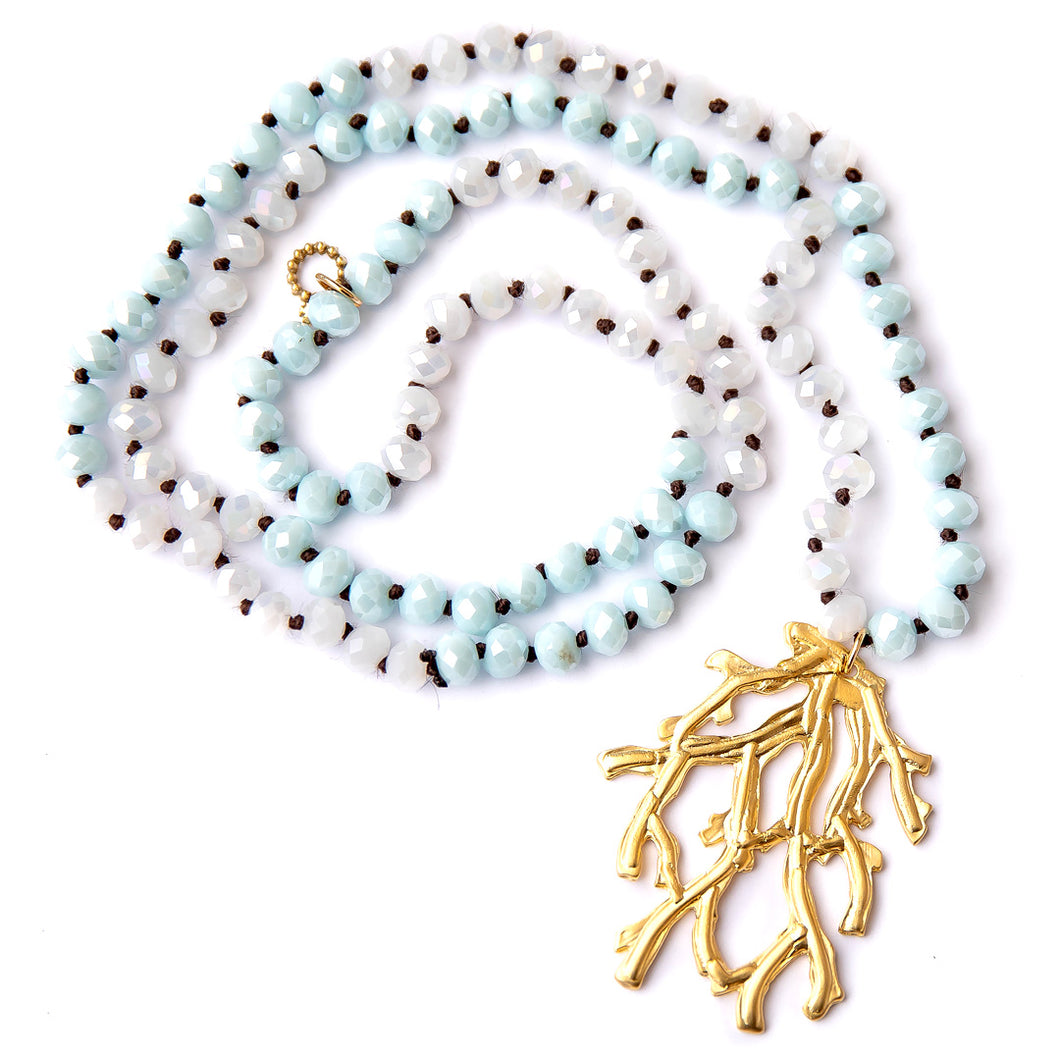 Hand tied faceted two tone aqua and white quartz gemstone necklace paired with a brass coral leaf pendant