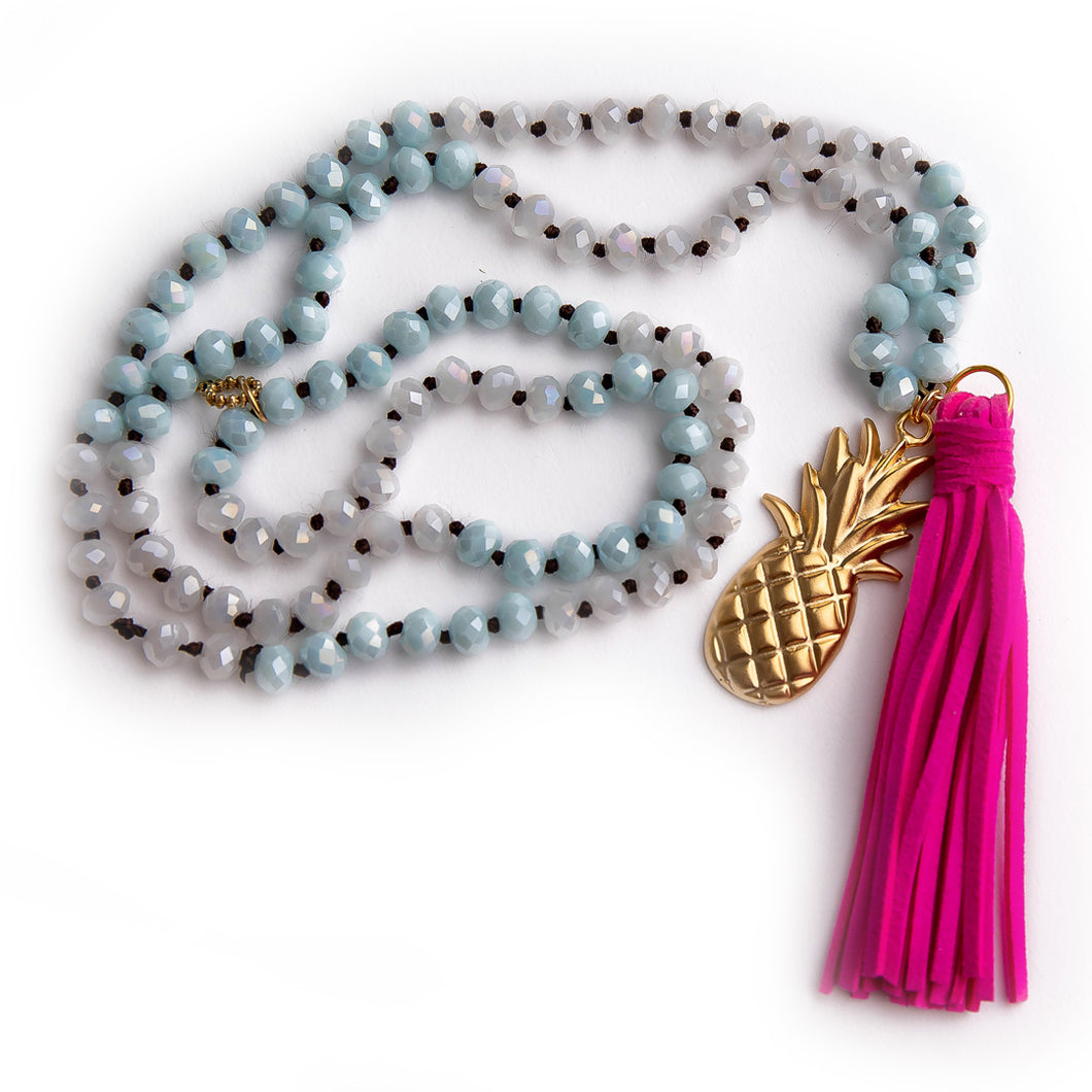 Hand tied faceted two tone aqua and white quartz gemstone necklace paired with a hot pink leather tassel featured with a brass pineapple