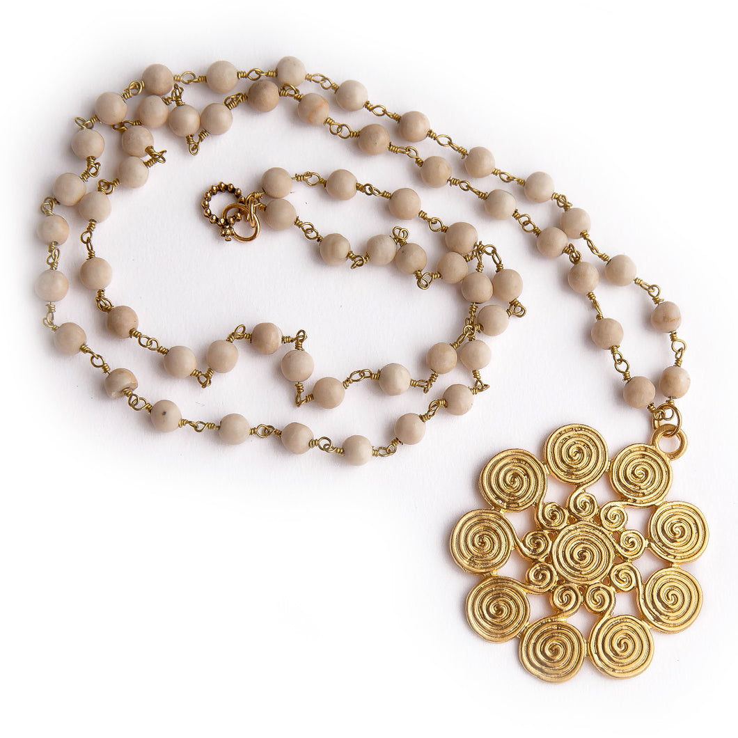 Cream coral rosary chain paired with a gold spiral pendant