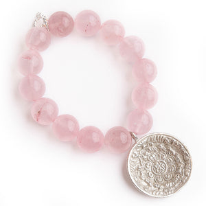 Rose quartz paired with a small silver prayer bowl