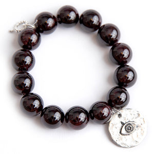 Garnet paired with a silver hammered evil eye