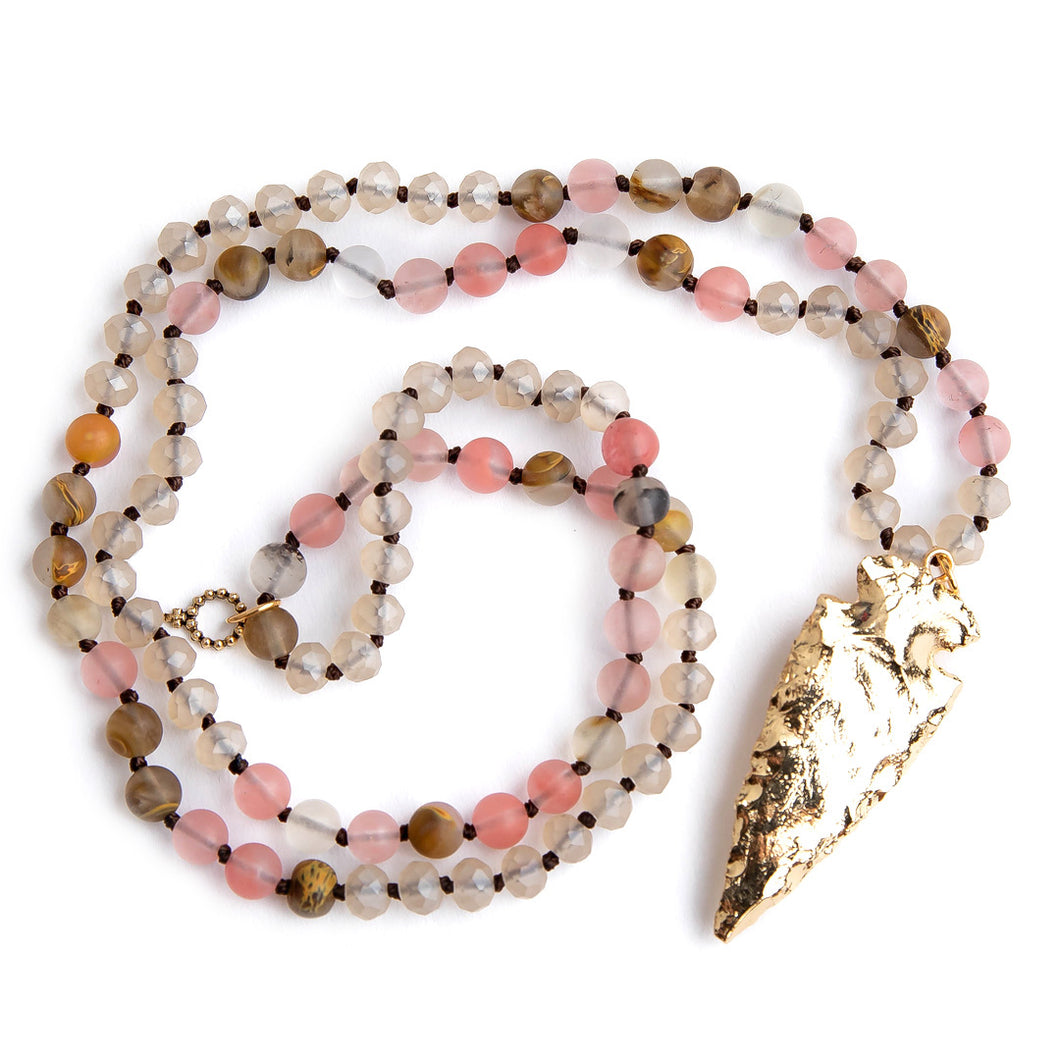 Hand tied matte cherry quartz gemstone necklace paired with a brass arrowheard