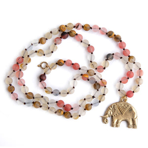 Hand tied matte cherry quartz gemstone necklace paired with a bronze elephant