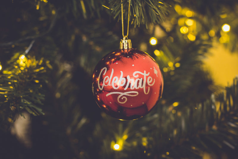 A 'celebrate' Christmas ornament hanging on a tree