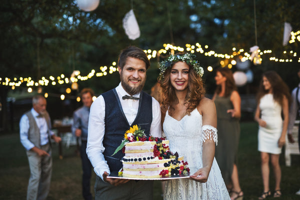 A couple holding a cake at an outdoor wedding reception