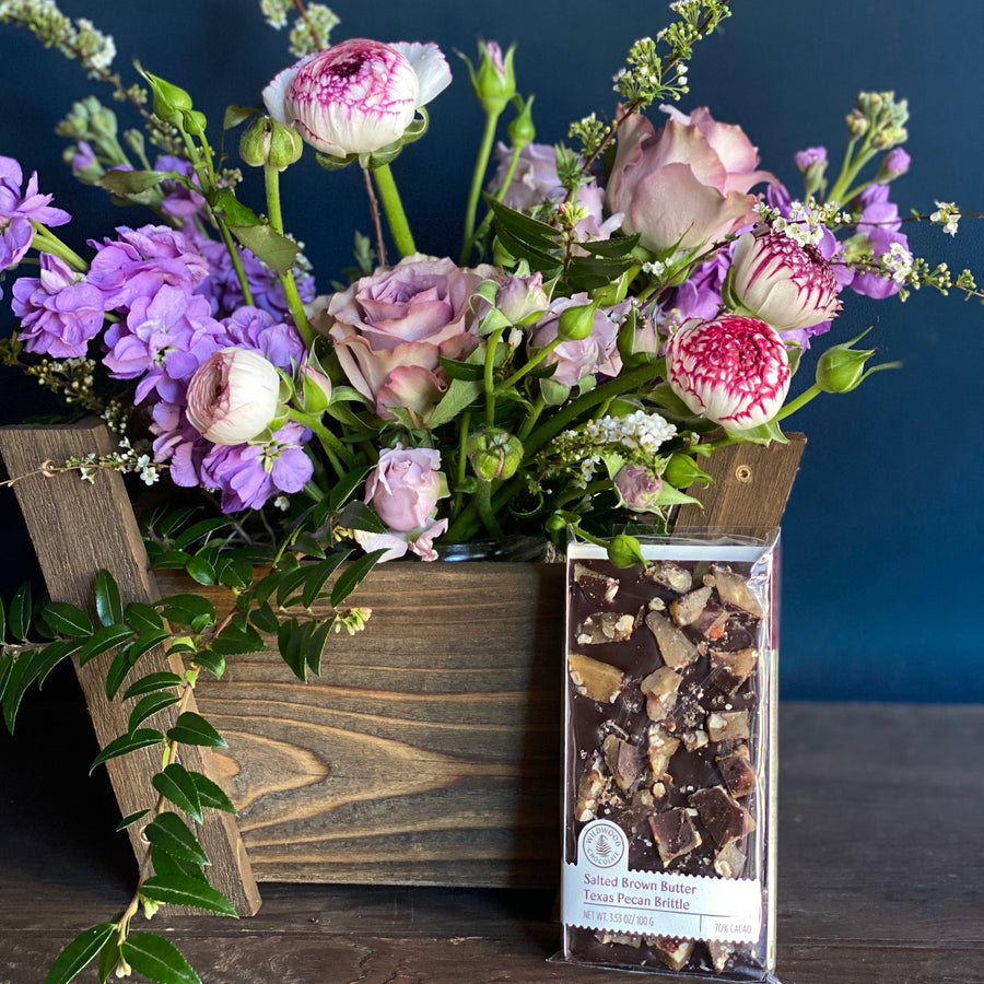 A seasonal floral designed in a handmade wooden basket accompanied with a bar of award winning chocolate by Portland chocolatier Wildwood Chocolate.