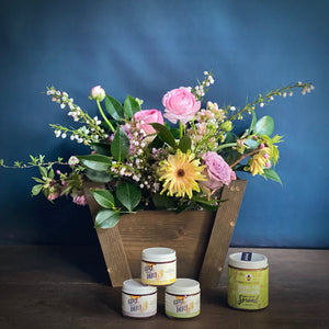 A floral designed in a wooden gift basket accompanied by Girl Meets Dirt mini spoon preserves and a jar of pear cardamom honey cream spread. Local delivery in the Greater Seattle area.