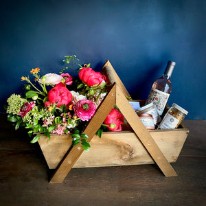 A gift basket of spa items and flowers designed in a handmade wooden basket by Seattle Florist Campanula Design Studio. Available for same day delivery.