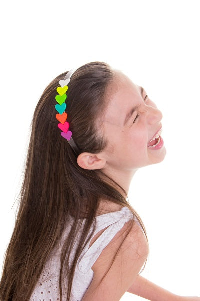 A girl laughs while wearing our centipede heart headband in neon pink.