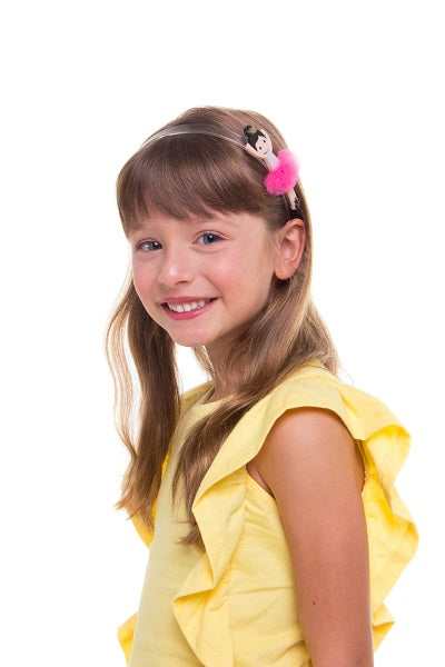 Girl in a yellow top and wearing our ballerina headband featuring yellow hair and a pink tulle skirt.