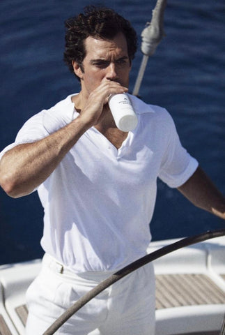 Henry Cavill drinking a bottle of No1 Rosemary Water whilst steering a boat