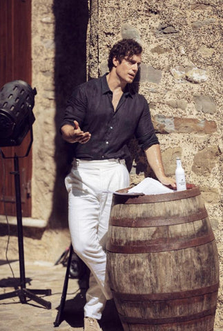 Henry Cavill standing next to a barrel learning his lines