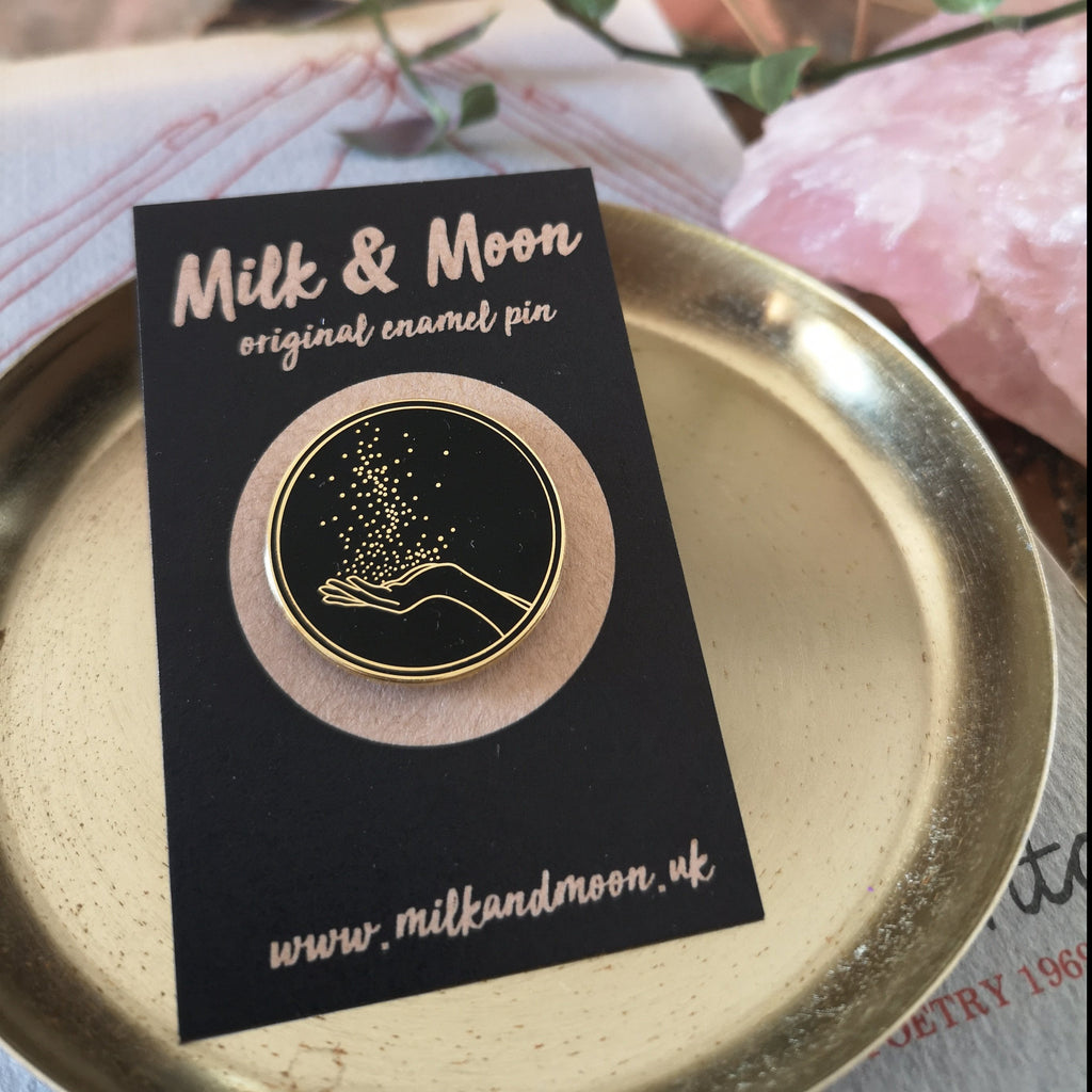 Milk and Moon Magic hard enamel pin , a black and gold circular enamel pin featuring an open hand in gold. There are sparkles rising from the open palm.