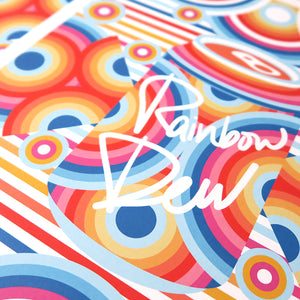 Rainbow Dew is a pop art print that has a multitude of colours. Red, blue, yellow, magenta, sun flower yellow. There are concentric circles that are arranged in a radial way with a drink can in the centre.