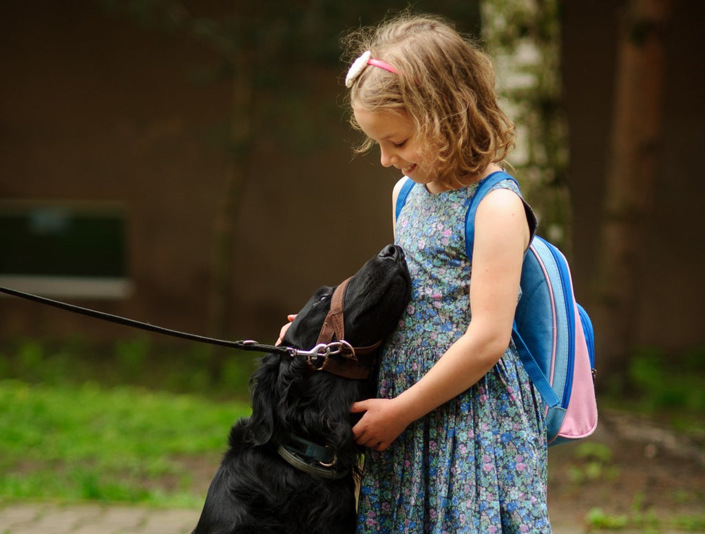 dog-nuzzling-smiling-girl-with-backpack-going-to-school